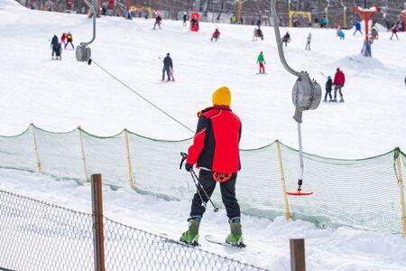 Skiers skiing climb a yoke on a mountain. Light skiing track in Bakuriani. Winter resort. Фото со стока
