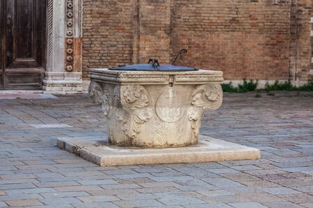 Ancient stone well for rain water in a square in Venice, Italy Standard-Bild