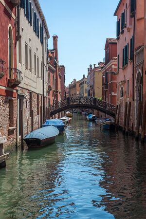 View of narrow Canal with boats and gondolas in Venice, Italy. Venice is a popular tourist destination of Europe Stok Fotoğraf