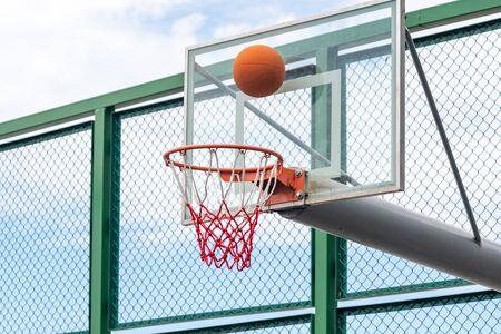 Basketball ring with a net and ball, outdoor playground
