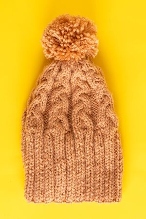 Handmade knitted winter hat on yellow background, female hat Stock Photo