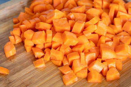Diced carrots on wooden chopping board, food