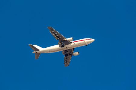 Large passenger plane flying in the blue sky. Transportation Reklamní fotografie