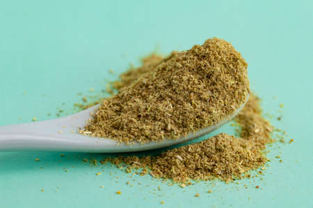 Ground Fenugreek in ceramic spoon, spices for food. flavor
