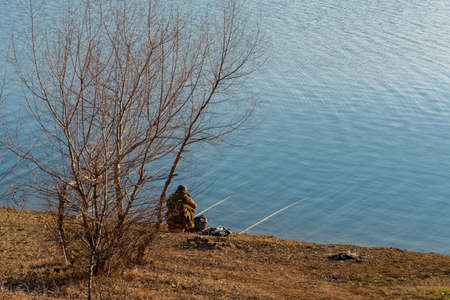 Fisherman with a fishing rod sitting on the shore. Nature