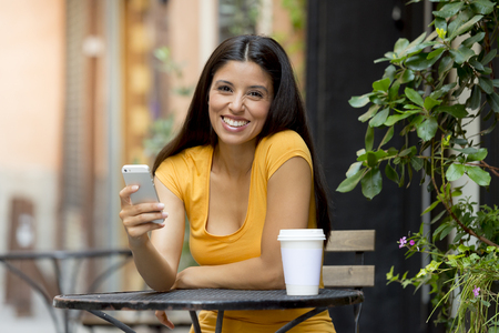 rumour: attractive latin woman in her twenties happy and excited on her smart phone