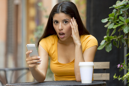 displeased: attractive latin woman in her twenties shocked while reading a tex message on her smart phone at a coffeeshop