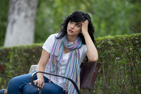 attractive beautiful latin woman sitting on a park bench feeling sad and depressed in a park outside in europe 스톡 콘텐츠