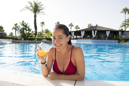 happy attractive latin woman wearing a bikini drinking a cocktail or orange juice in swimming pool at a resort on holidays. Stock Photo