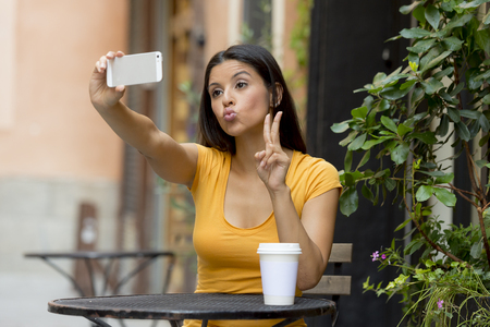 attractive latin woman twenties happy taking a selfie while having a coffee.
