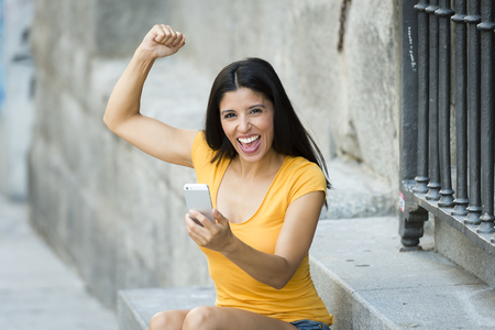 Happy young latin woman talking and texting on smart phone winning an online action, wearing casual clothes sitting in with a take away coffee in a urban bench    Stock Photo