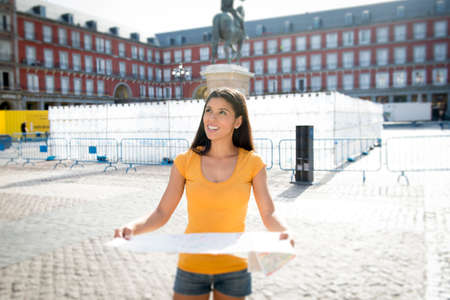 attractive latin woman on her twenties happy and excited in Plaza Major looking at a map. Stock Photo