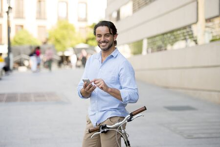 young happy attractive hispanic man in casual trendy clothes smiling cheerful using mobile phone on vintage cool retro bicycle in modern stylish lifestyle urban style concept