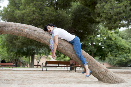 Pretty attractive woman wearing causal clothes over worked and stressed feeling relaxed sleeping in a tree in a green park. Stock Photo