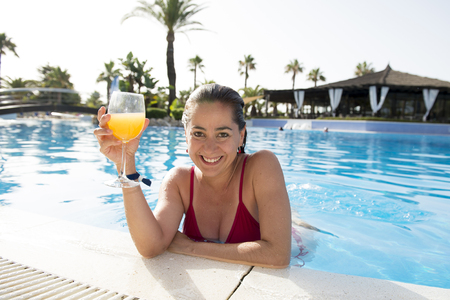 happy attractive latin woman wearing a bikini drinking a cocktail or orange juice in swimming pool at a resort on holidays.