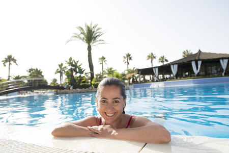 Pretty happy latin woman smiling on the edge of and swimming pool on holidays at a resort.
