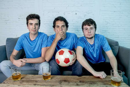 young group of caucasian football fans disappointed watching a football game on the couch.