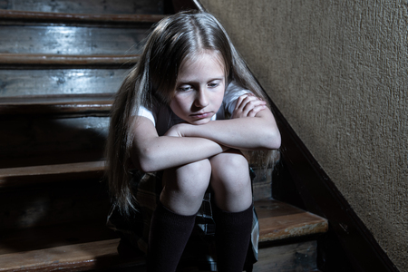Sad, depressed, unhappy schoolgirl suffering from bullying and abuse feeling lonely and hopeless sitting on stairs with dark light. School isolation, bullying, harassment and abuse concept