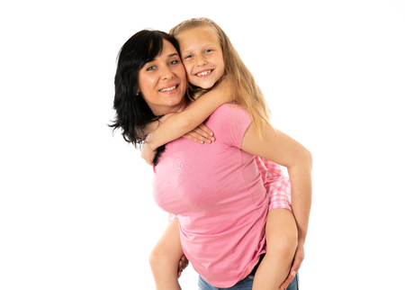 Portrait of a happy mother and cute blonde little girl hugging and looking cheerful at the camera in studio on white background. Happy family and good and positive parent and child relationship Stock Photo