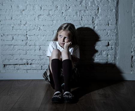 Sad desperate young girl suffering from bulling and harassment felling lonely, unhappy desperate and hopeless sitting against the wall, dark light. School isolation, abuse and bullying concept