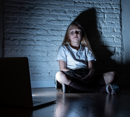 Scared sad girl bullied on line with laptop suffering cyberbullying and harassment feeling desperate and intimidated. Child victim of bullying stalker social media network
