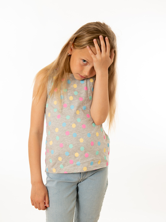 Portrait of a pretty bullied, depressed, alone, tired, stressed young child looking unhappy and sad. Isolated withe background. Human emotions, facial expressions, body language and bulling