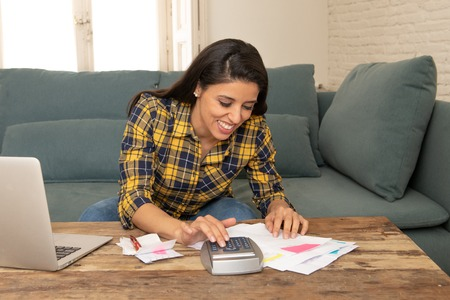 Happy attractive latin woman calculating home finances, accounting costs, charges, taxes, mortgage and paying bills at home using calculator and laptop looking cheerful and relax Standard-Bild