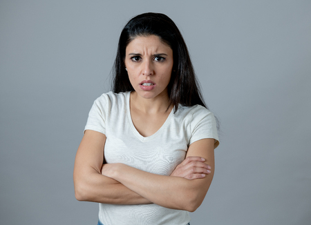 Close up portrait of an attractive young latin woman with an angry face. looking furious and moody with an intense look showing anger and rage. Human facial expressions and emotions Foto de archivo