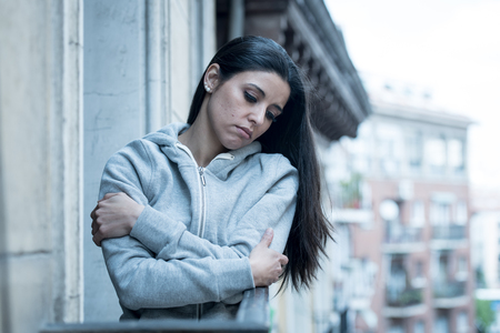 Attractive latin depressed lonely woman staring out feeling sad, pain, grief on a balcony at home. Crisis, depression and mental health concept