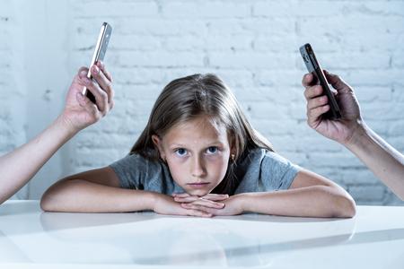moeder en vader met behulp van mobiele telefoon verwaarlozen kleine verdrietige genegeerde dochter verveeld en eenzaam gevoel verlaten en teleurgesteld in ouders mobiele mobiele smartphone verslaving slecht gedrag concept