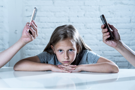 mother and father using mobile phone neglecting little sad ignored daughter bored and lonely feeling abandoned and disappointed in parents mobile cell smart phone addiction bad behavior concept Stock Photo