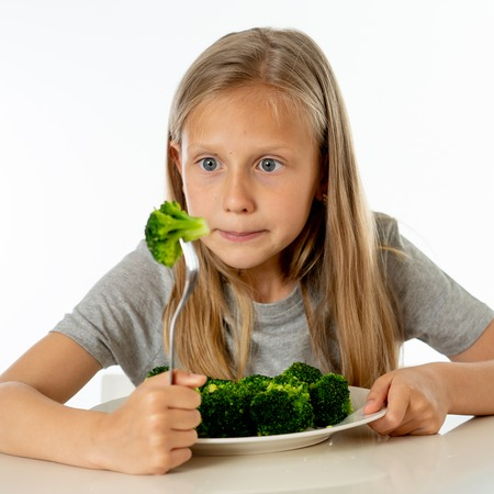 Nutrition & healthy eating habits for kids healthy eating concept. Children do not like to eat vegetables. Little cute kid girl refuse to eat healthy broccoli vegetables on a white background Foto de archivo - 103584986