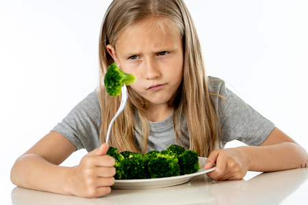 Nutrition & healthy eating habits for kids healthy eating concept. Children do not like to eat vegetables. Little cute kid girl refuse to eat healthy broccoli vegetables on a white background Foto de archivo - 103584988