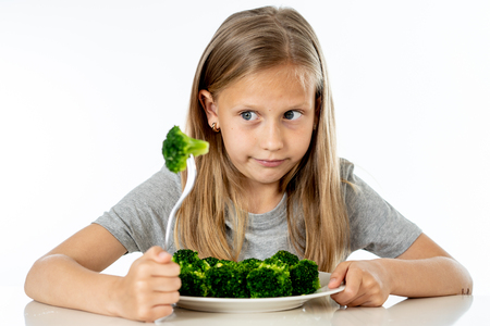 Nutrition & healthy eating habits for kids healthy eating concept. Children do not like to eat vegetables. Little cute kid girl refuse to eat healthy broccoli vegetables on a white background Foto de archivo - 103584990