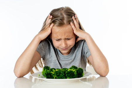 Nutrition & healthy eating habits for kids healthy eating concept. Children do not like to eat vegetables. Little cute kid girl refuse to eat healthy broccoli vegetables on a white background Foto de archivo - 103586359