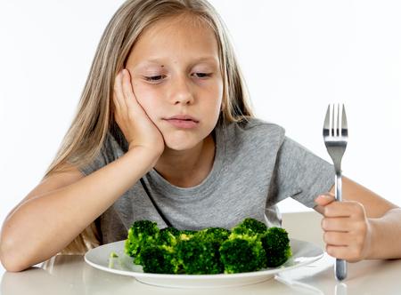 Ernährung & gesunde Essgewohnheiten für Kinder gesunde Ernährung Konzept. Kinder essen kein Gemüse. Kleines niedliches Kindermädchen weigern sich, gesundes Brokkoli-Gemüse auf weißem Hintergrund zu essen Standard-Bild