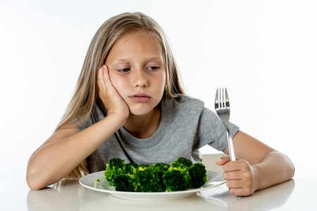 Nutrition & healthy eating habits for kids healthy eating concept. Children do not like to eat vegetables. Little cute kid girl refuse to eat healthy broccoli vegetables on a white background Foto de archivo - 103586362