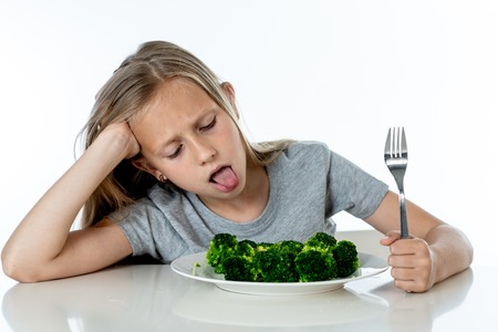 Nutrition & healthy eating habits for kids healthy eating concept. Children do not like to eat vegetables. Little cute kid girl refuse to eat healthy broccoli vegetables on a white background