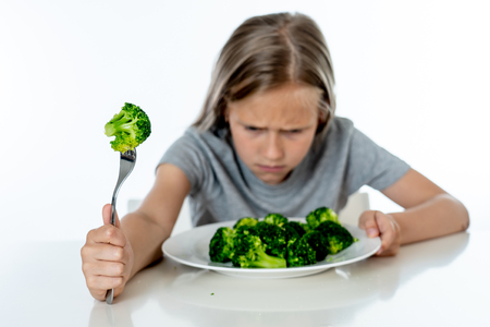 Nutrition & healthy eating habits for kids healthy eating concept. Children do not like to eat vegetables. Little cute kid girl refuse to eat healthy broccoli vegetables on a white background Foto de archivo - 103586368