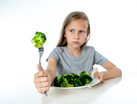 Nutrition & healthy eating habits for kids healthy eating concept. Children do not like to eat vegetables. Little cute kid girl refuse to eat healthy broccoli vegetables on a white background Foto de archivo - 103586370