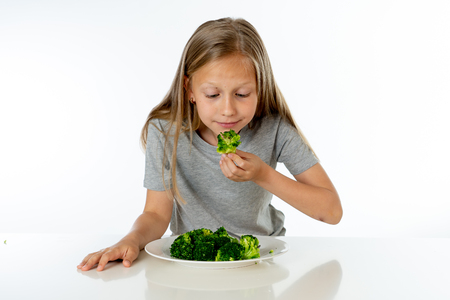 Nutrition & healthy eating habits for kids healthy eating concept. Children do not like to eat vegetables. Little cute kid girl refuse to eat healthy broccoli vegetables on a white background Foto de archivo - 103586938
