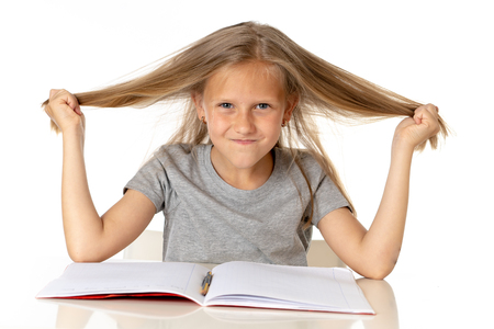 sweet young little schoolgirl pulling her hair desperate in stress while sitting on school desk doing homework tired and exhausted screaming crazy isolated on white background in education concept 免版税图像
