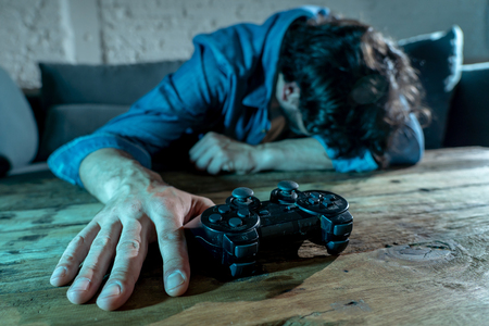 Addiction and dependency concept. close up on young mans hand with pad joystick playing video games Male addicted to console gaming concept.