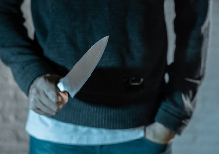 close up of a hands holding a knife of dangerous hooded man standing in the dark in London knife crime concept. Zdjęcie Seryjne - 103595597
