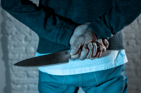 close up of a hands holding a knife of dangerous hooded man standing in the dark in London knife crime concept. Reklamní fotografie - 103595607
