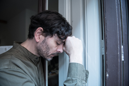 Lonely young man looking outside house balcony looking depressed, destroyed, sad and suffering emotional crisis and grief thinking of taking a difficult and important life decision