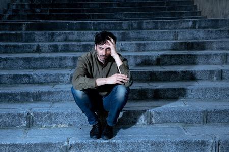 lateinamerikanischer Mann gestresst von der Arbeit auf Stufen außerhalb sitzen Angst bei Erwachsenen Ursache von Depressionen und Lebensproblemen, die Sie einsam, traurig und besorgt im Konzept der psychischen Gesundheit fühlen Standard-Bild
