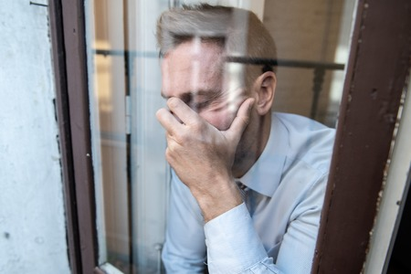 Close up portrait of middle aged man sad and depressed looking through the window refection, thinking about his life suffering depression in mental health concept 写真素材