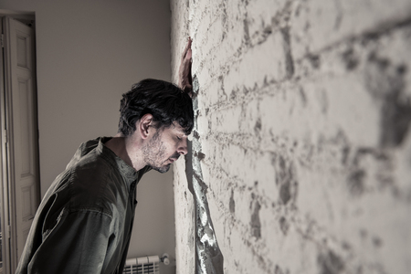 depressed man leaning up on a white wall in dark room at home, feeling sad, tired and anxious in a mental health depression concept.