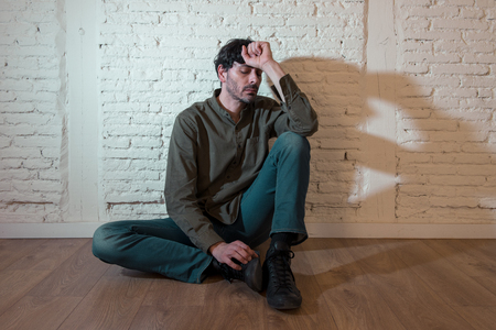 young depressed man sitting against a white wall at home with a shadow on the wall feeling miserable, lonely and sad in mental health depression concept